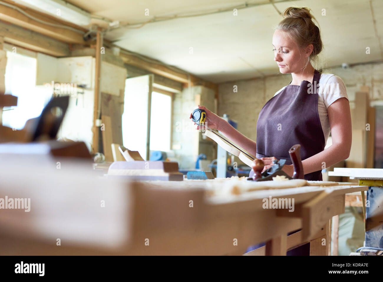 Female Carpenter Working in Shop - Stock Image