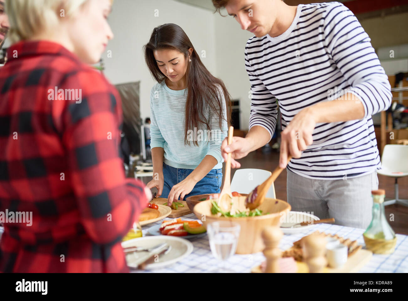 Friends Setting Up Dinner Table - Stock Image