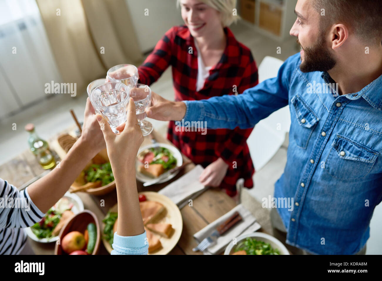 Friends Clinking Glasses at Thanksgiving Dinner - Stock Image