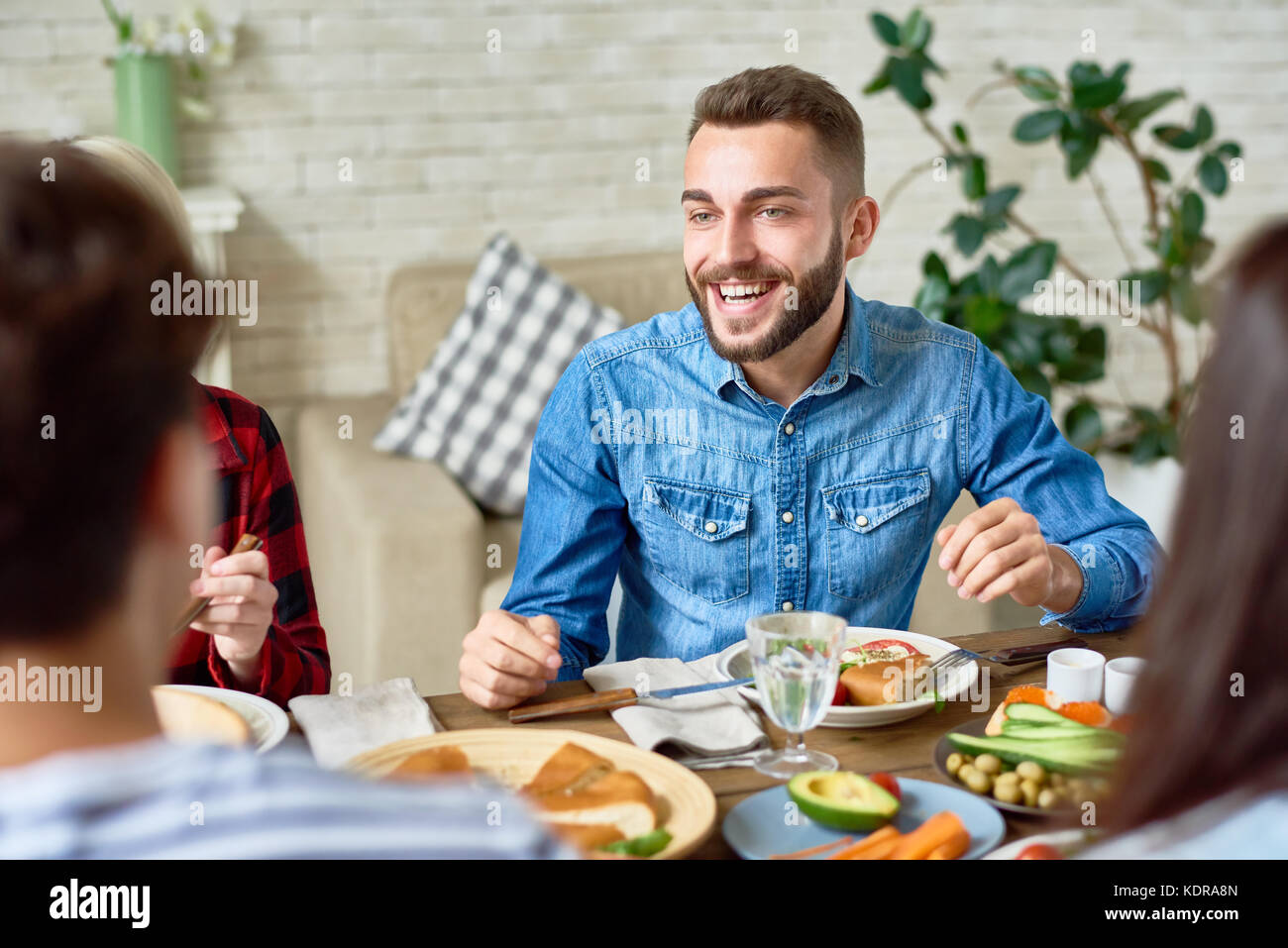 Young Man Enjoying Dinner with friends - Stock Image