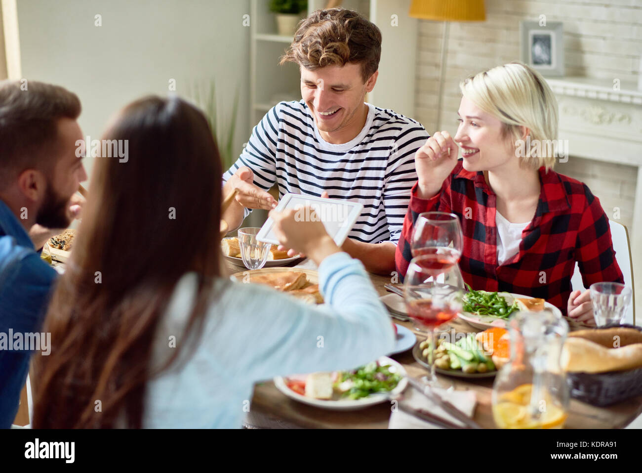 Young People Looking at Digital Tablet during Dinner - Stock Image