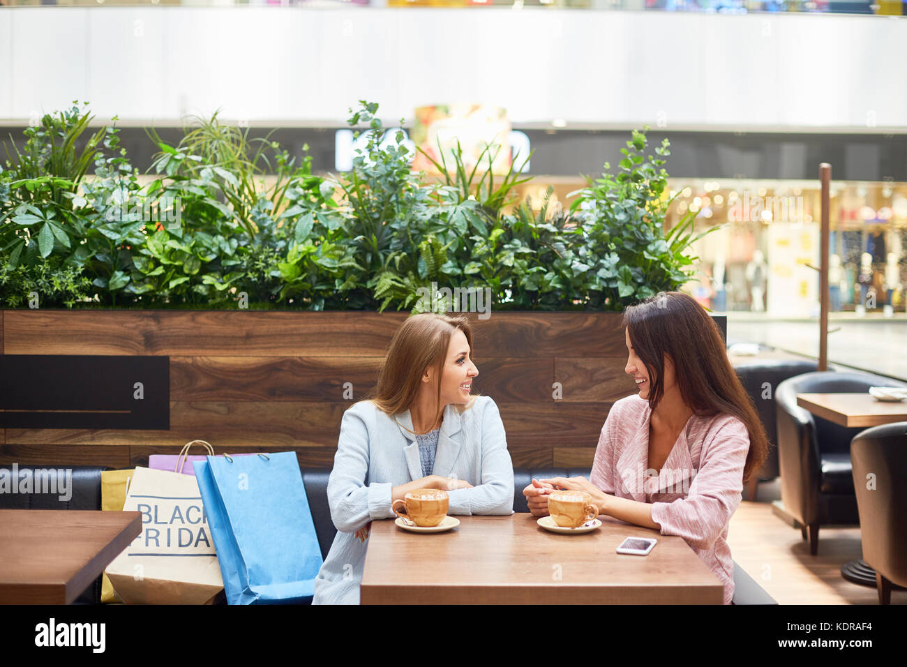 Young Women in Shopping Center Cafe - Stock Image