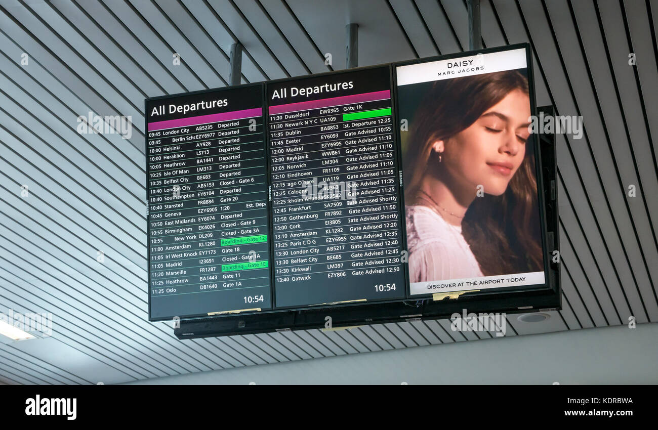 Departures of flights listed on electronic information board at Heathrow Terminal 5 with advert for Daisy perfume - Stock Image