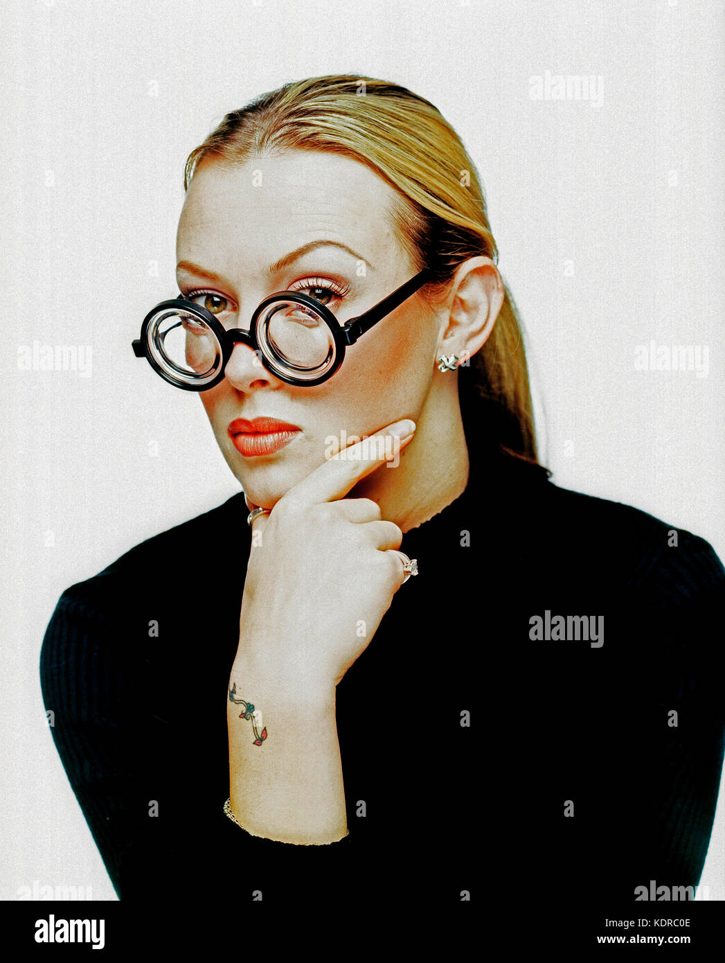 Young woman. Studio portrait. Thick lense spectacles. - Stock Image