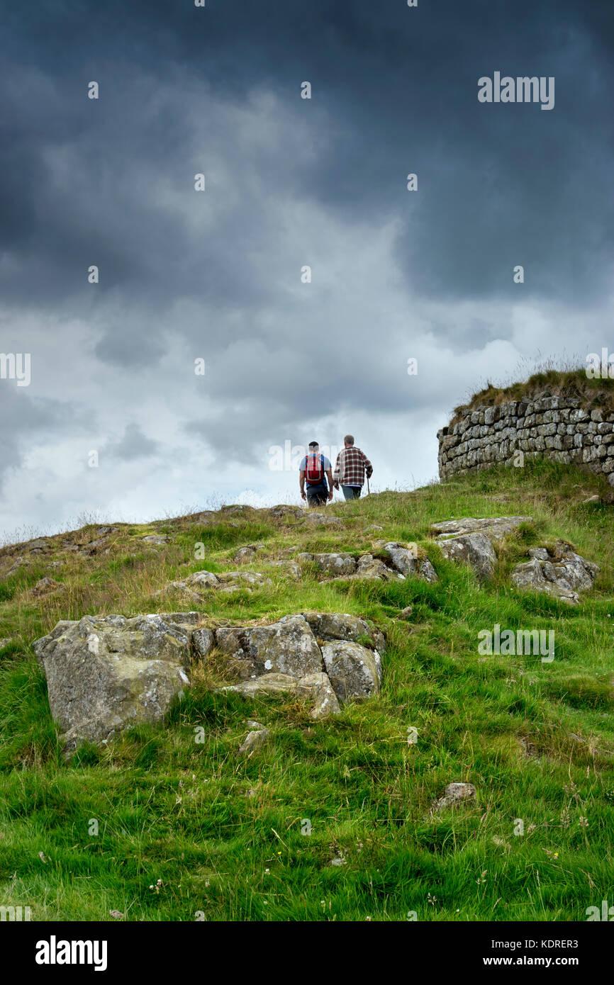 Hikers near Hadrian's Wall in Northumberland, England, UK - Stock Image