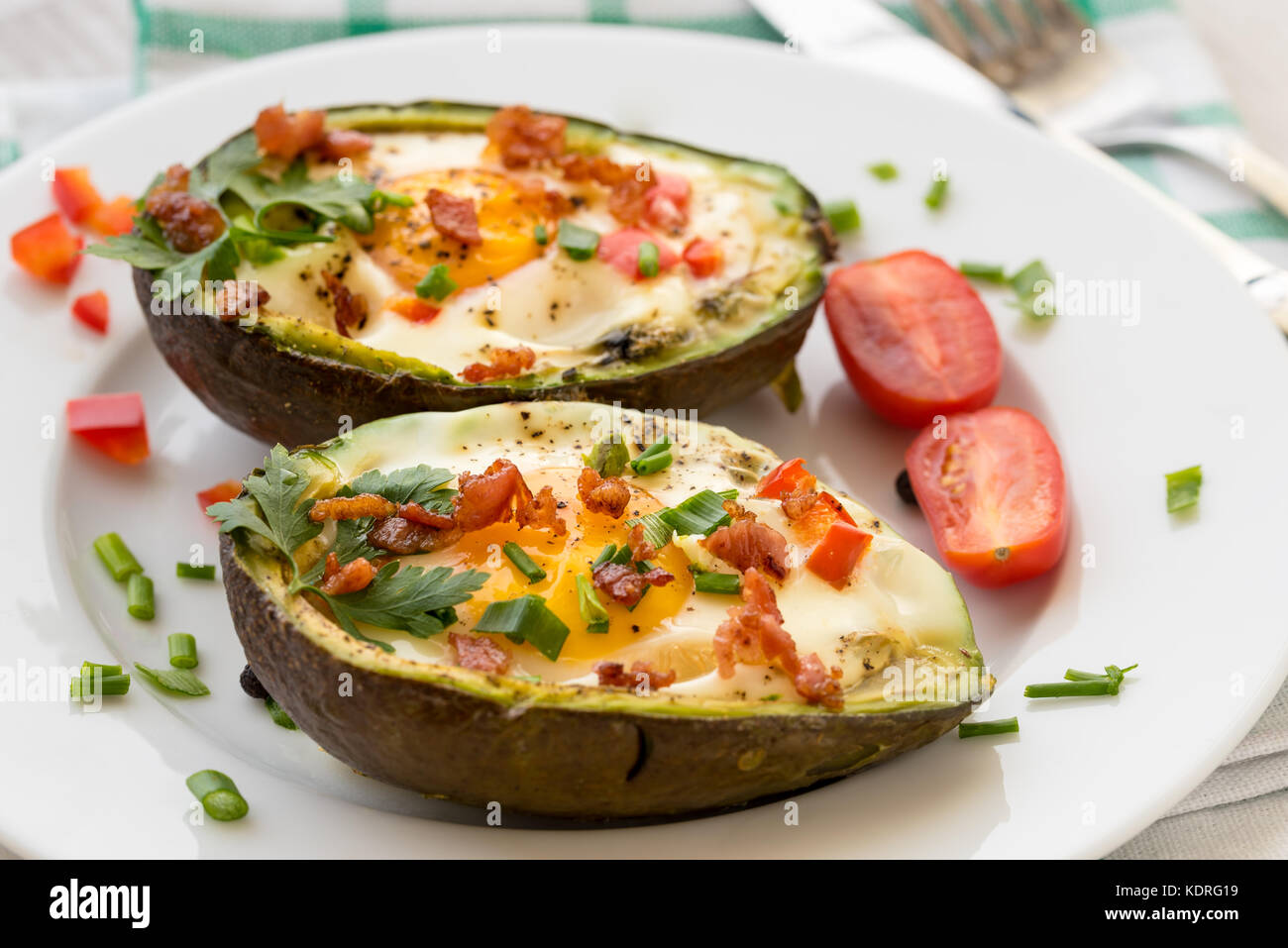 Eggs baked in avocado with bacon, red paprika and chive. Stock Photo
