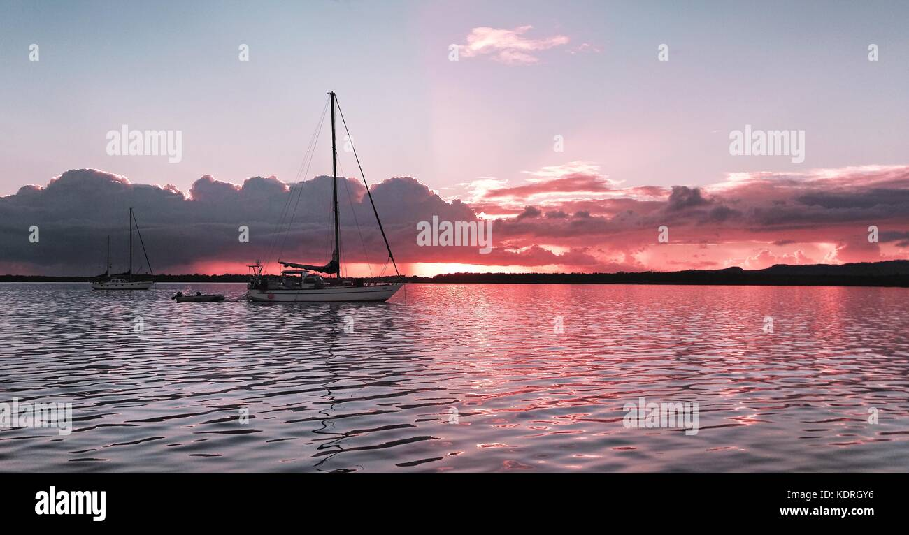 A striking inspirational nautical pink coloured cloudy saltwater lake sunset with water reflections. Captured on - Stock Image