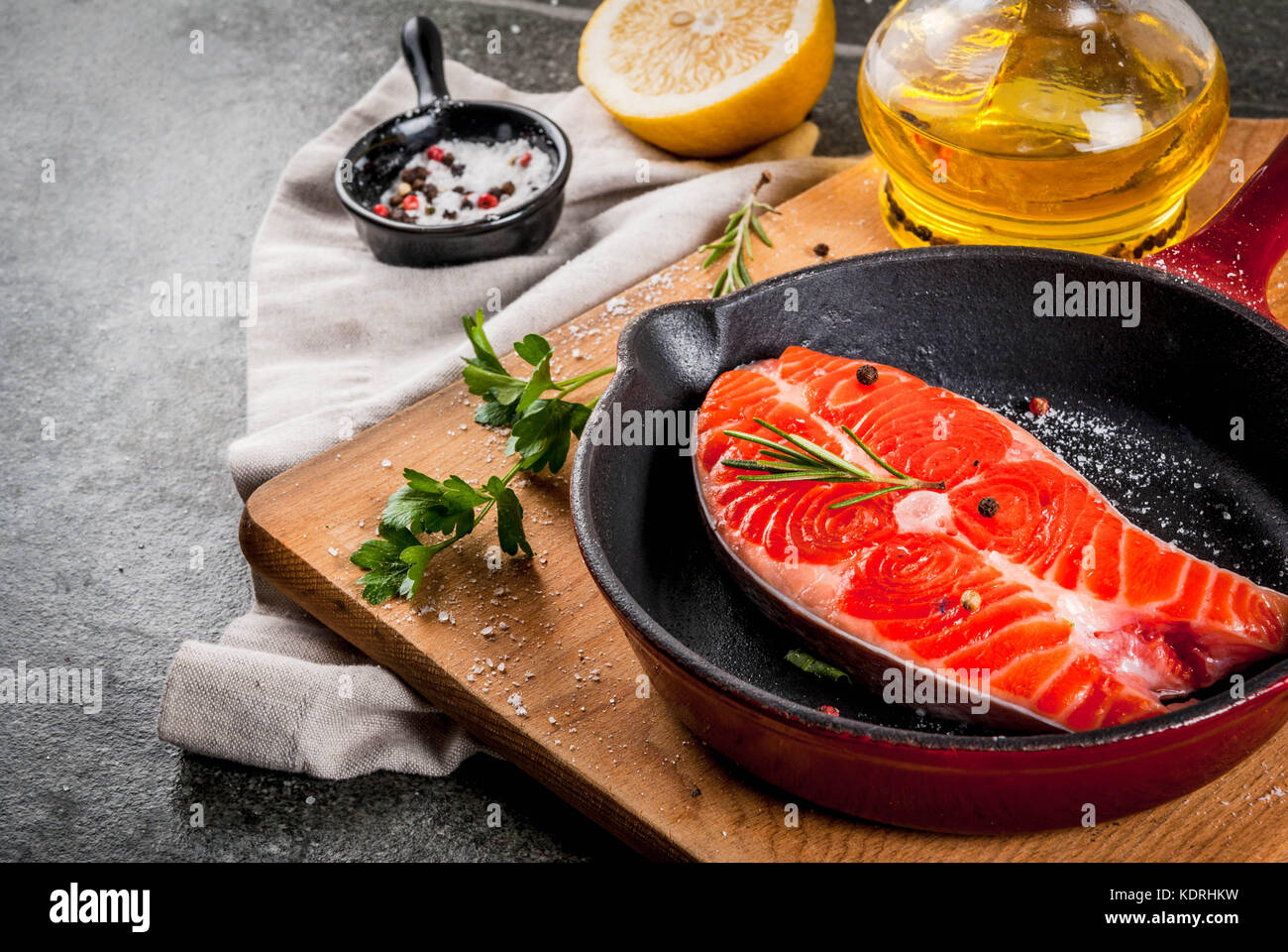 Raw fresh salmon fish with ingredients for cooking - olive oil, lemon, onion, parsley, rosemary, on frying pan, - Stock Image