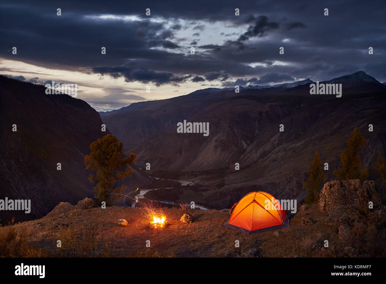 A illuminated tent and campfire in mountains in dawn - Stock Image