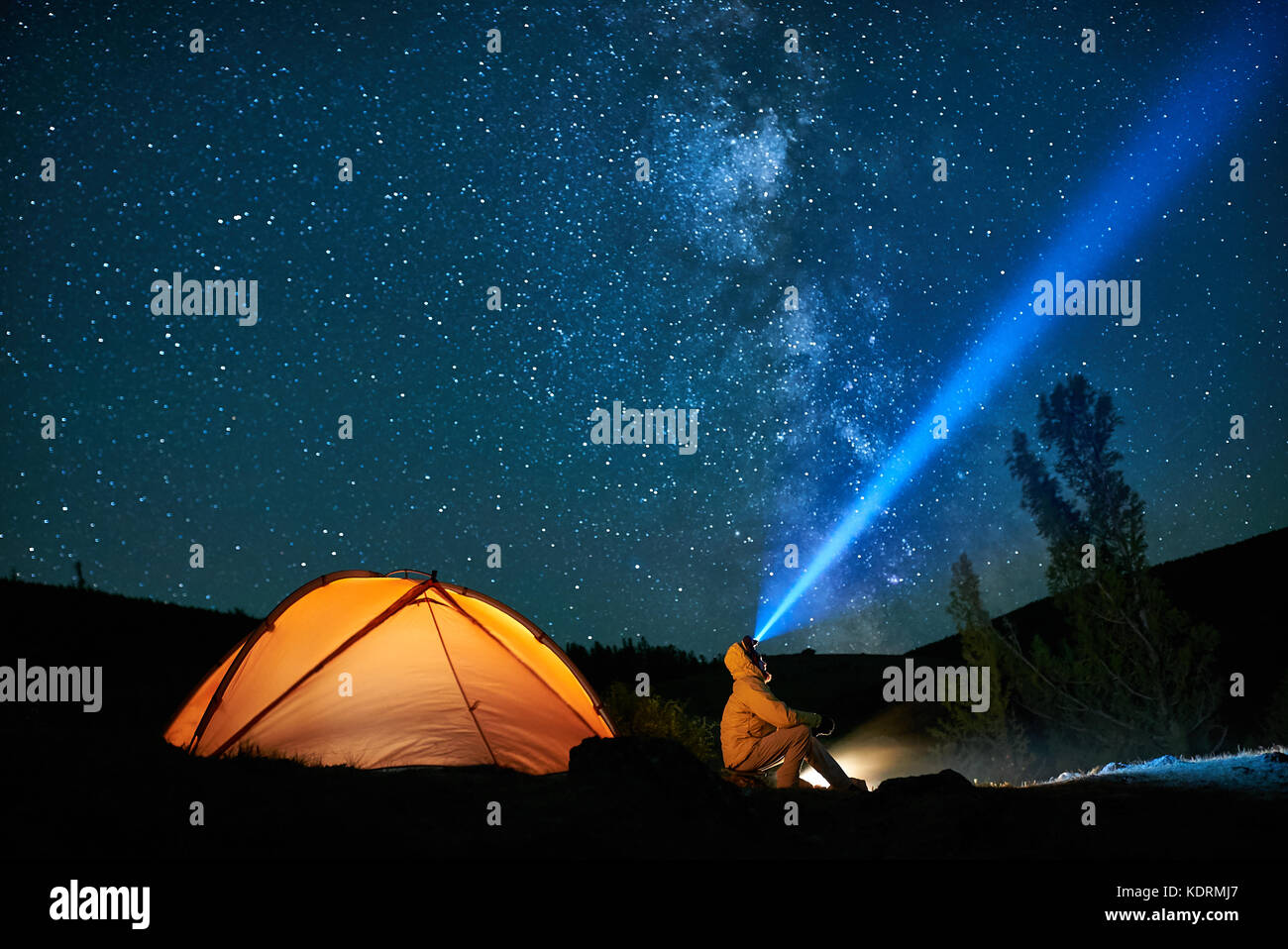 Man tourist with flashlight near his camp tent at night. - Stock Image