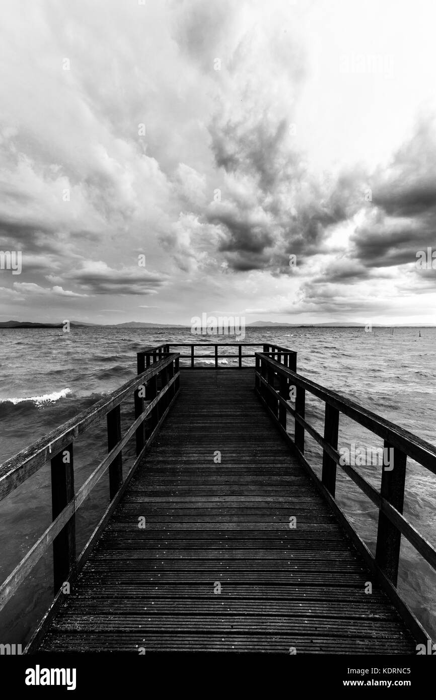 First person view of a pier on a lake on a moody day, with dark water and overcast, stormy sky - Stock Image