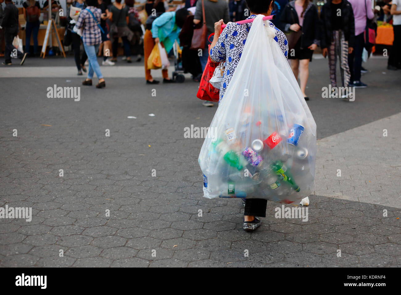 A person in the informal economy carrying a bag of bottles, cans, and recyclables. - Stock Image