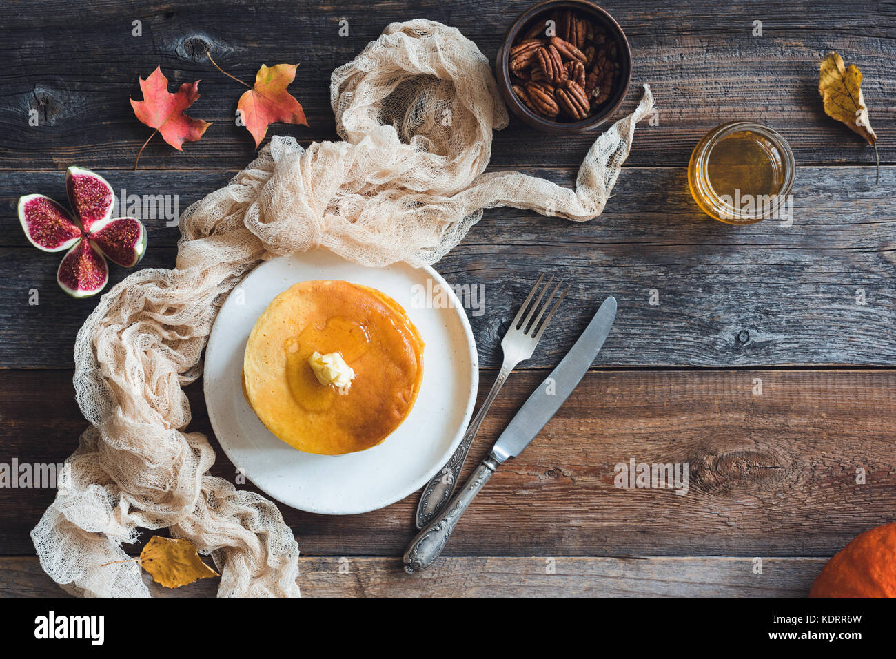 Pancakes with butter, pecan nuts, figs and honey on wooden table with copy space for text. Autumn food, pumpkin - Stock Image