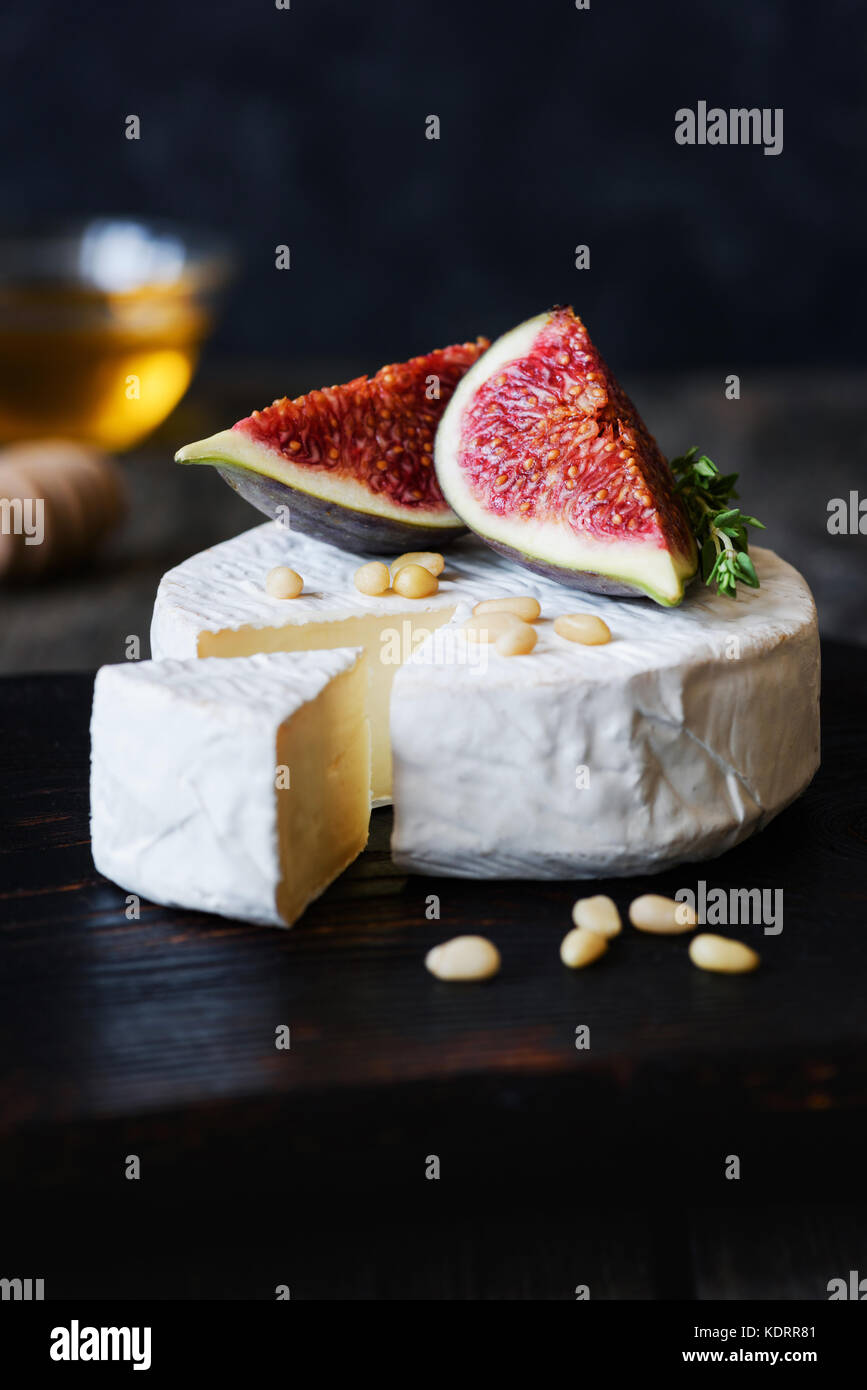 Brie, camambert cheese, fresh purple figs, nuts and honey on dark wooden backdrop. Closeup view, vertical - Stock Image
