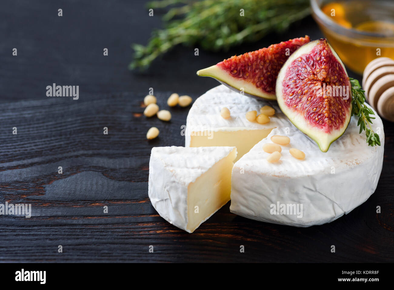White cheese brie or camambert. Gourmet appetizer cheese plate with white cheese, figs, thyme, honey and nuts - Stock Image