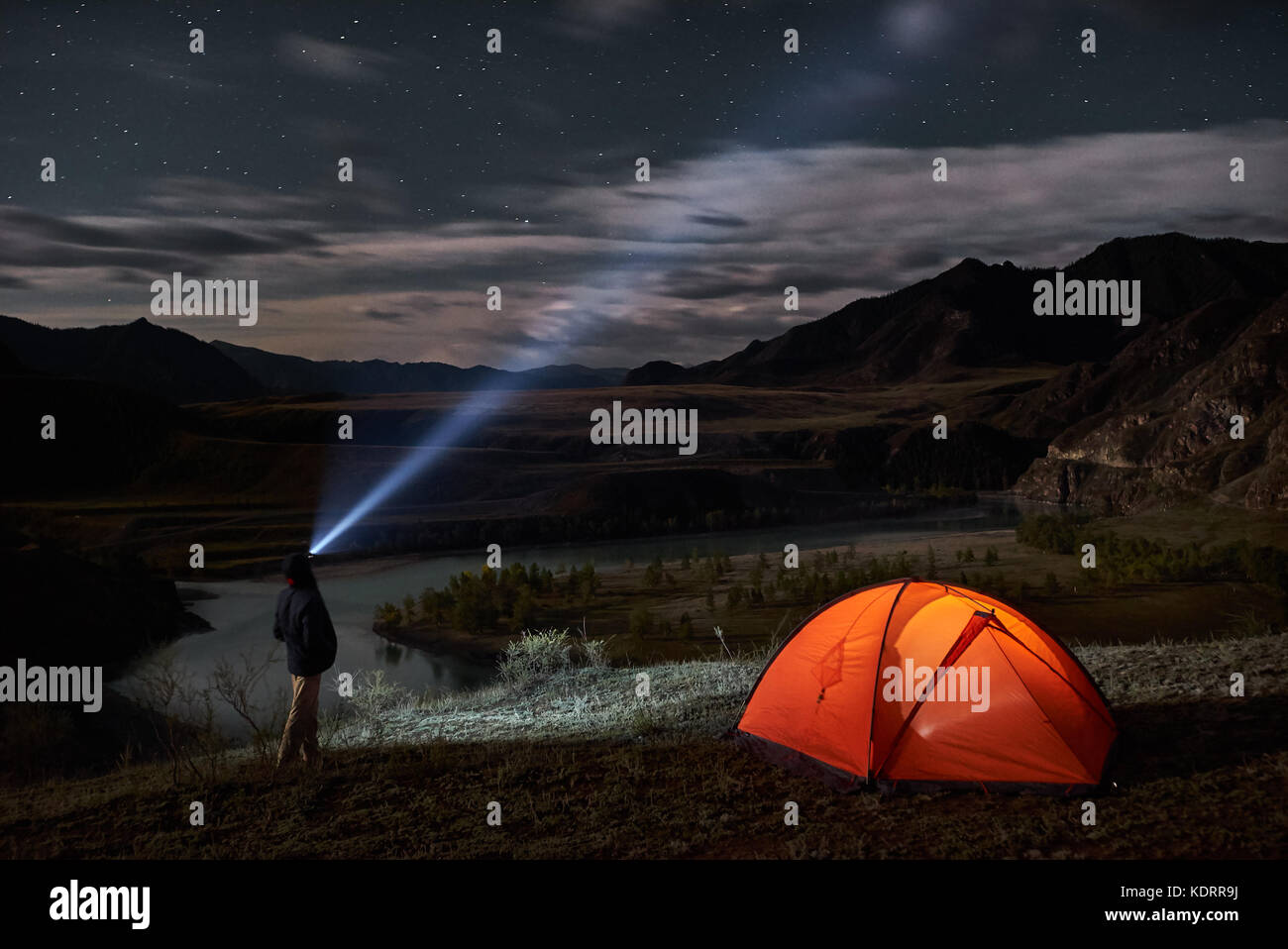 Male tourist with flashlight near his camp tent at night. - Stock Image