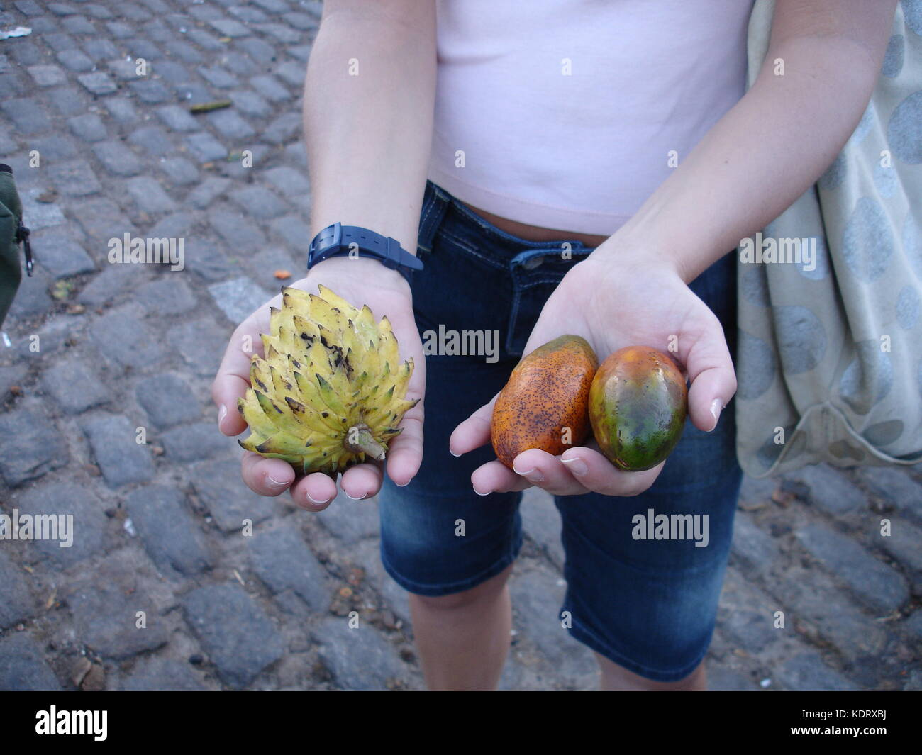 Woman holding three exotic fruits in her hands at ver o peso market in Belem, Brazil - Stock Image