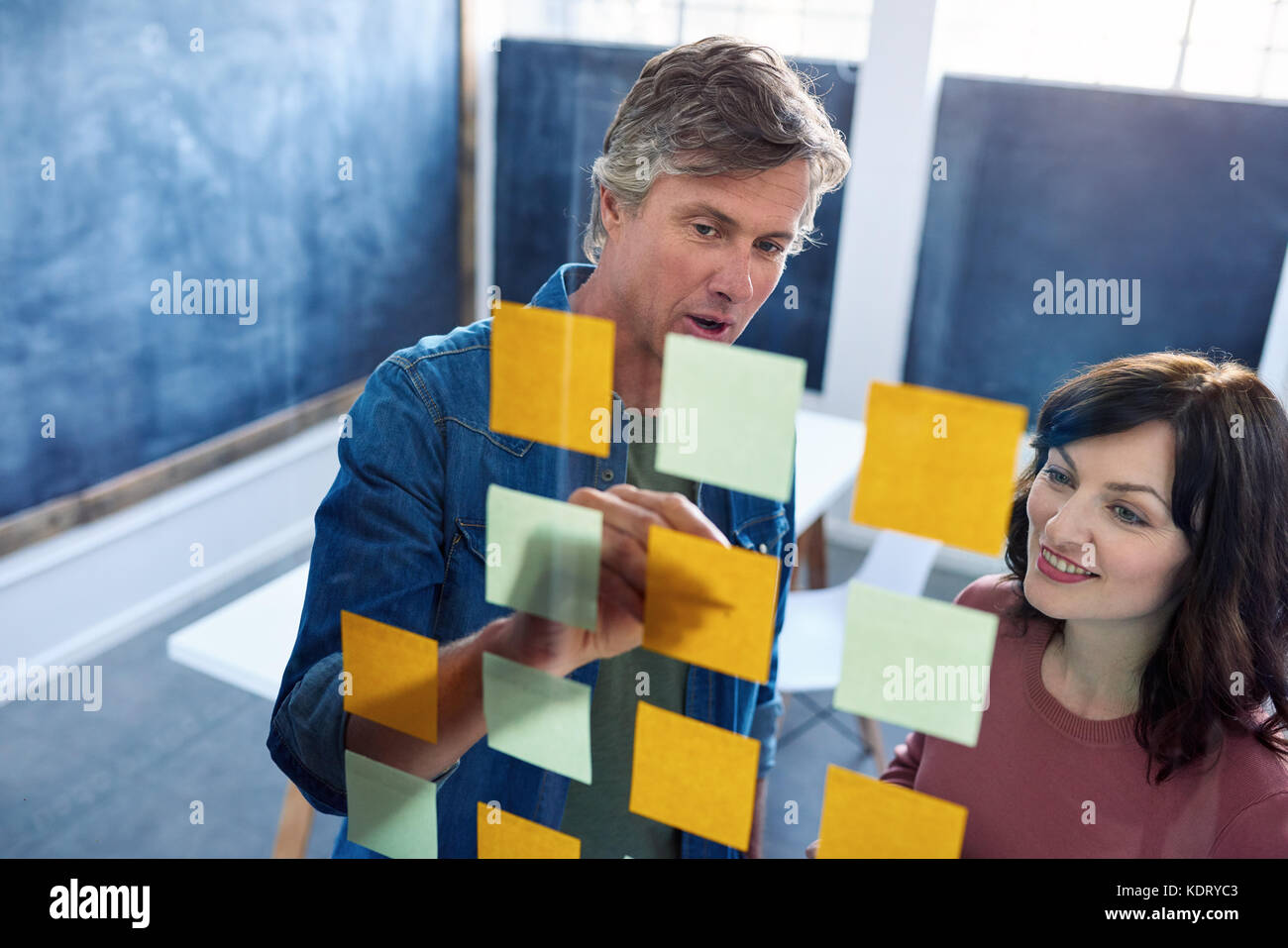 Smiling coworkers brainstorming on a glass wall in an office - Stock Image