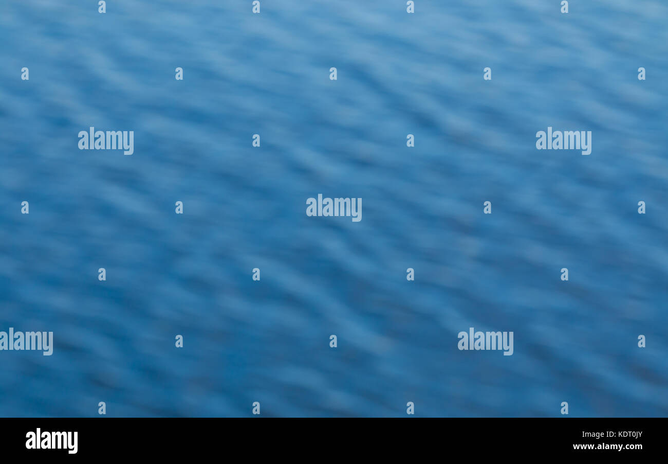 Blurred background of blue waves on the ocean showing soft textured wave pattern. - Stock Image