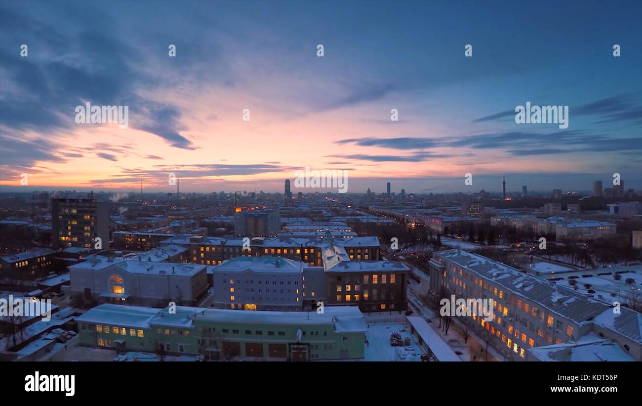 Evening city in winter timelapse. Evening city in winter view from roof timelapse. Panoramic view on the town and - Stock Image