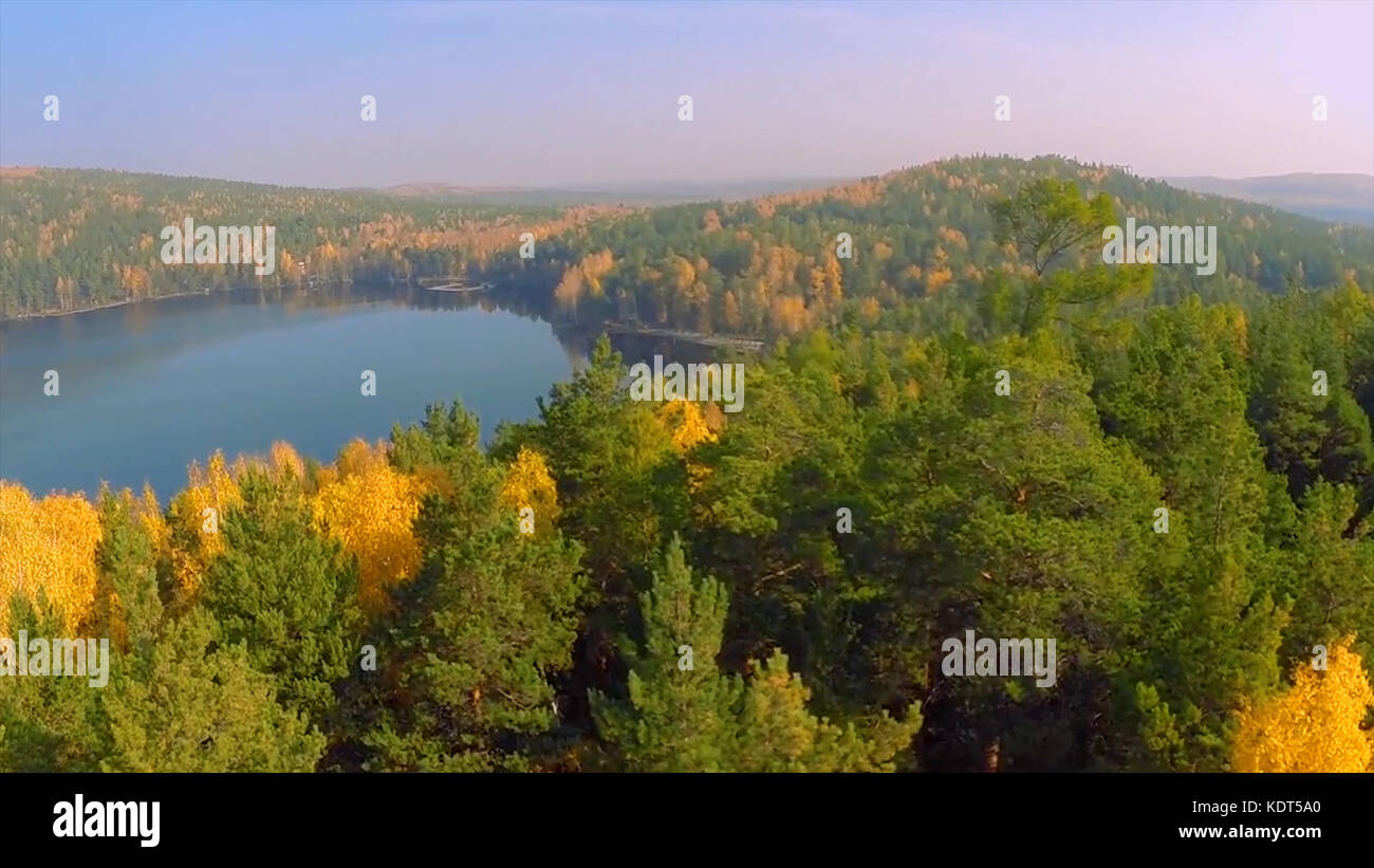 Forest in the fall lake in autumn view from the sky. Lake reflections of fall foliage. Aerial Colorful autumn foliage - Stock Image