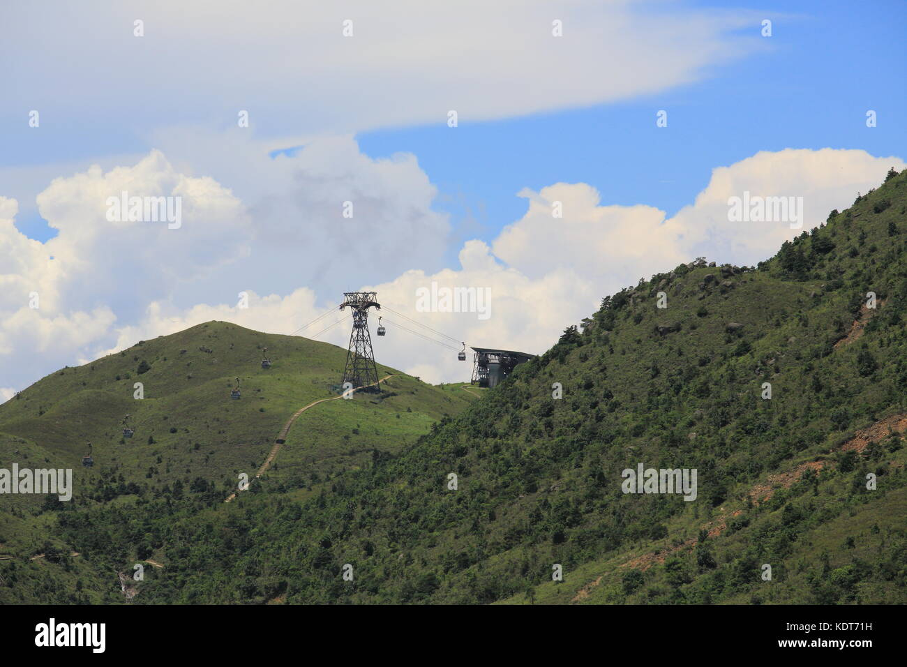 Ngong Ping 360 cable car tower with the cloudy landscape from Lantau Island in beautiful summer landscape - Stock Image