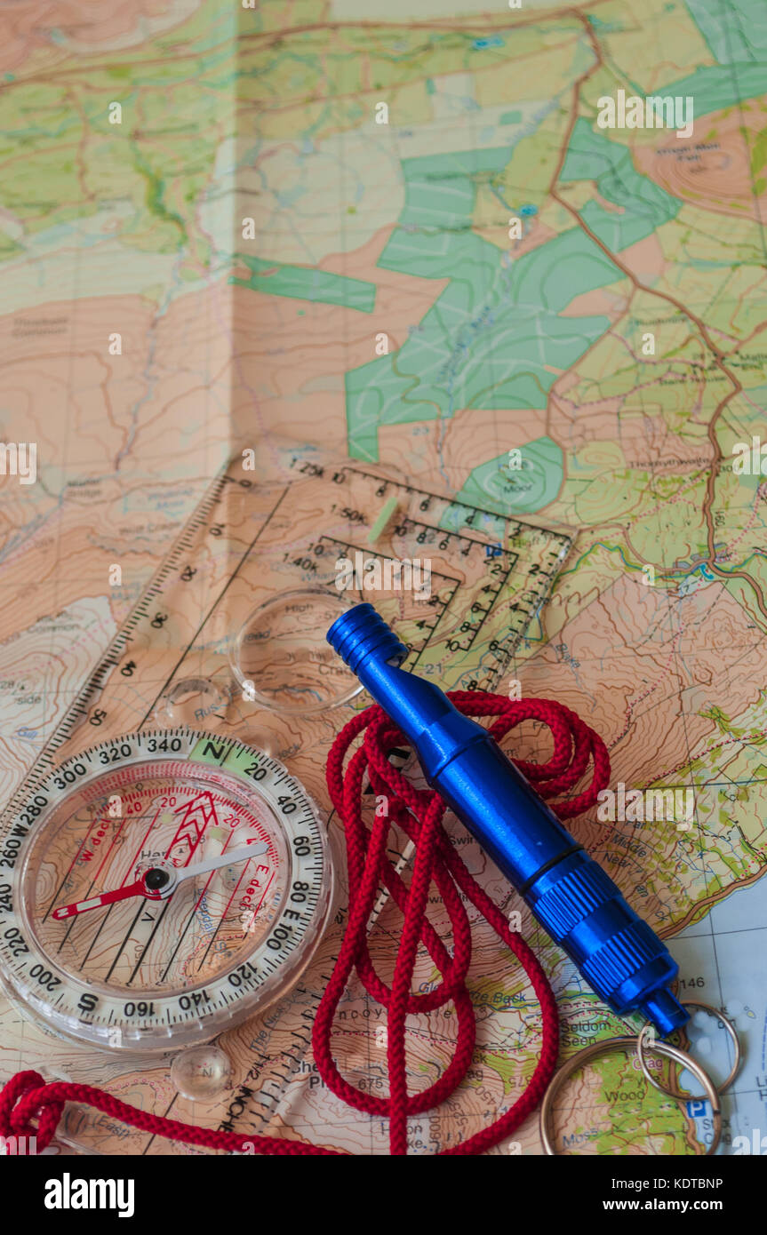 Compass showing direction on Topographic Map with Rescue Whistle, Navigation, Shallow Depth of Field, focus on North - Stock Image