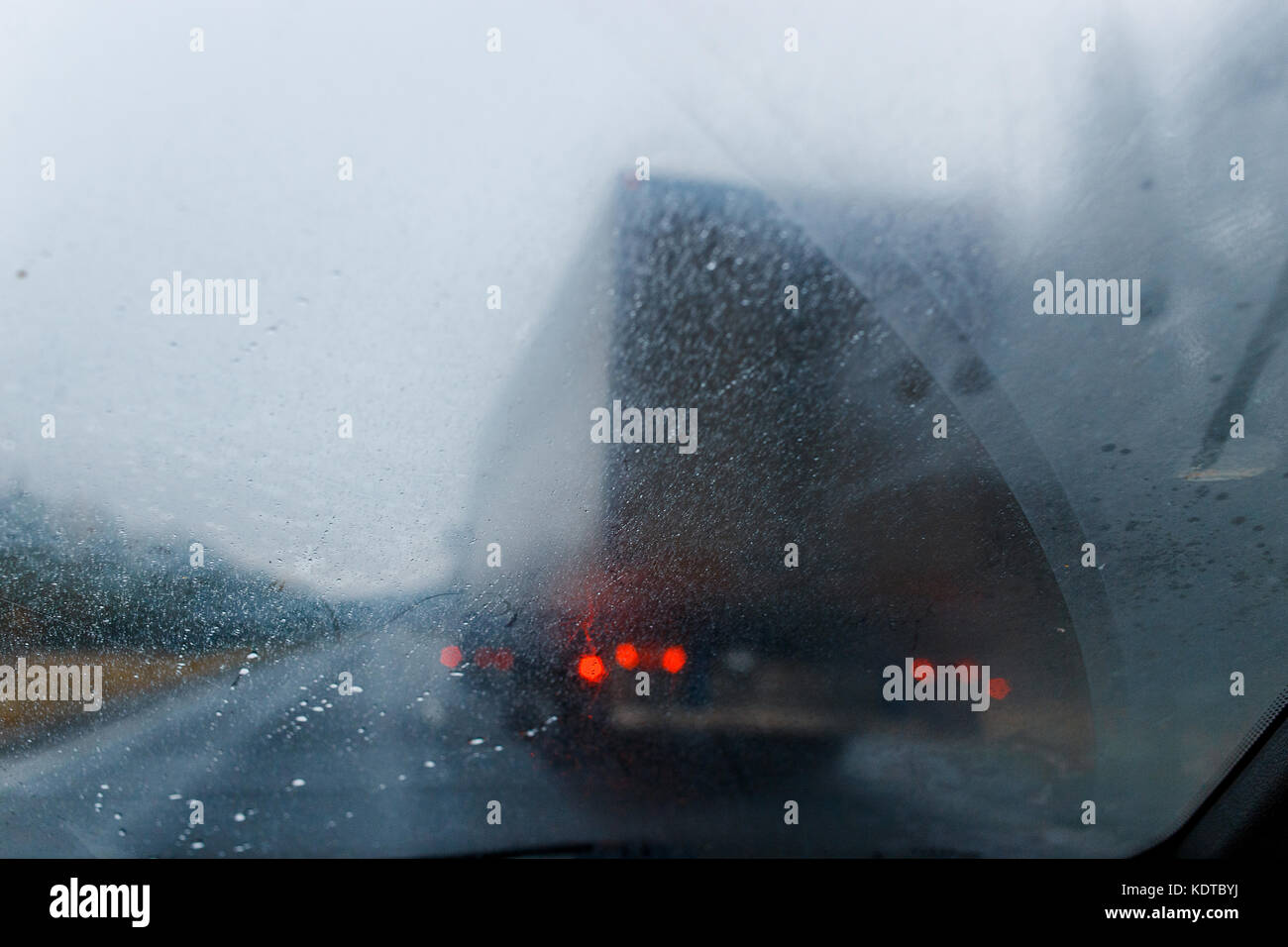 Rain drops on windscreen and blurred truck in forest road. Overtaking of the truck. Low visibility. - Stock Image