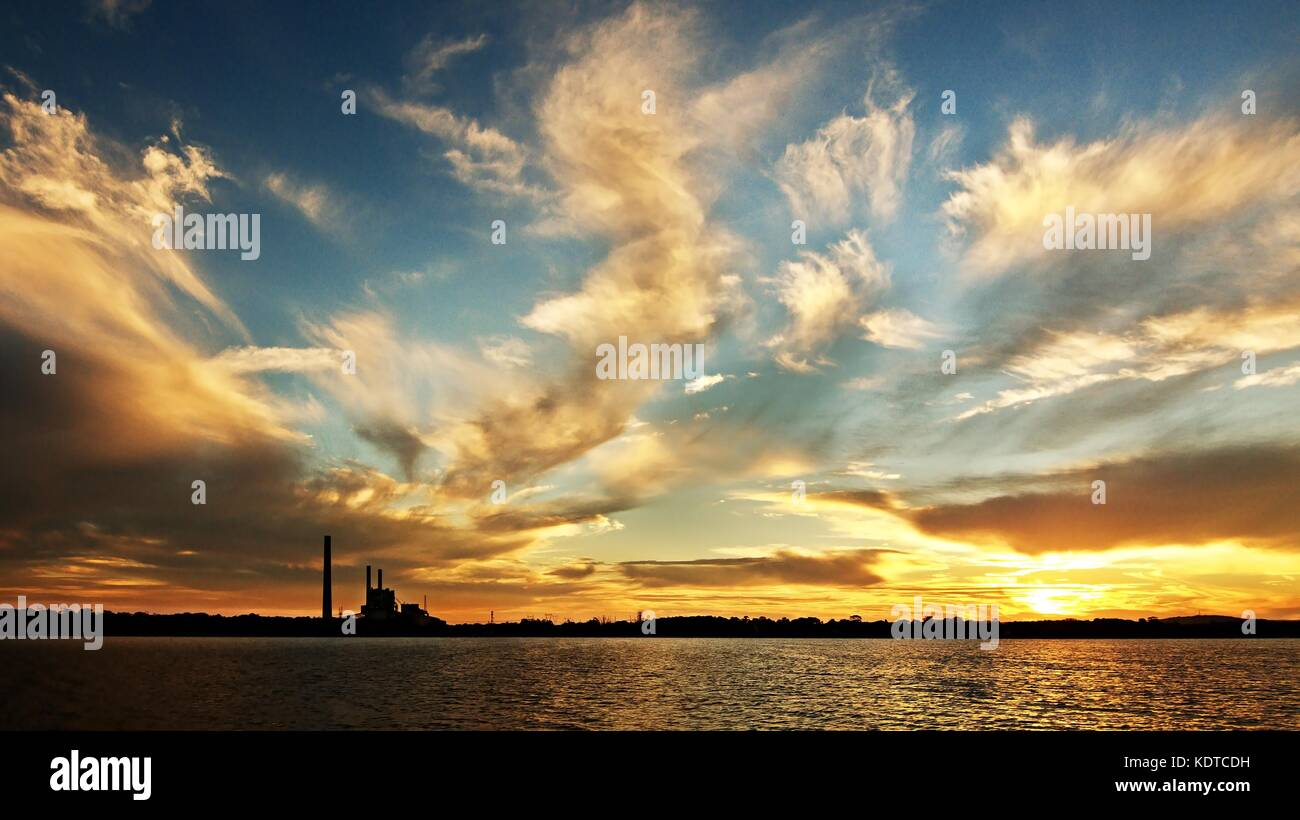 A striking inspirational gold coloured cloudy salt water lake sunset over a power station with water reflections. - Stock Image
