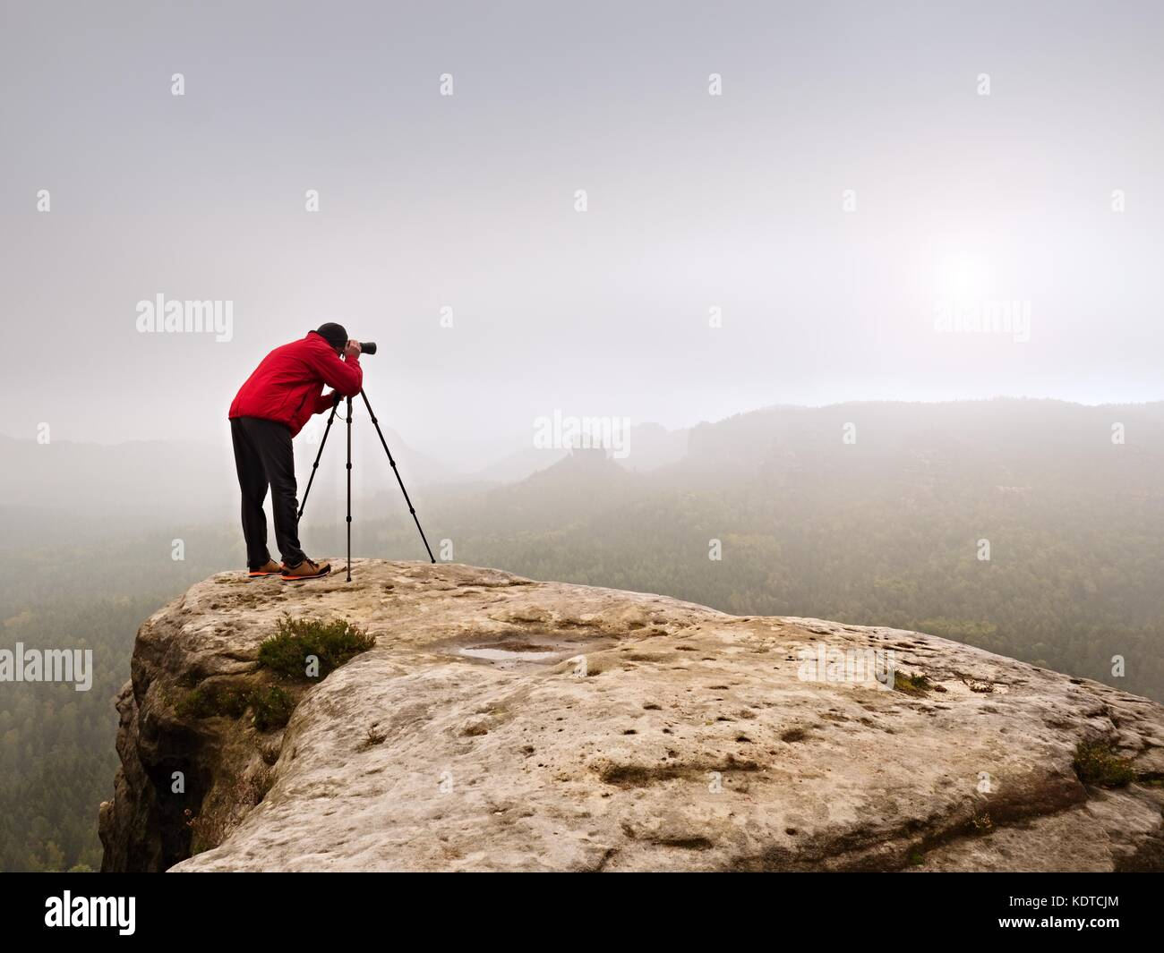 Photographr looking into viewfinder of dslr digital camera stand on tripod. Artist  photographing mountain and cloudy - Stock Image