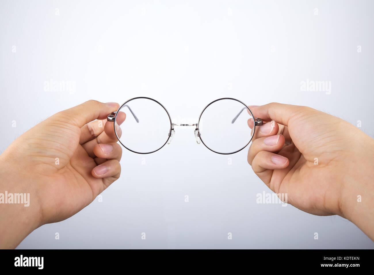 88089388c0335 hand holding circle glasses Stock Photo  163422217 - Alamy
