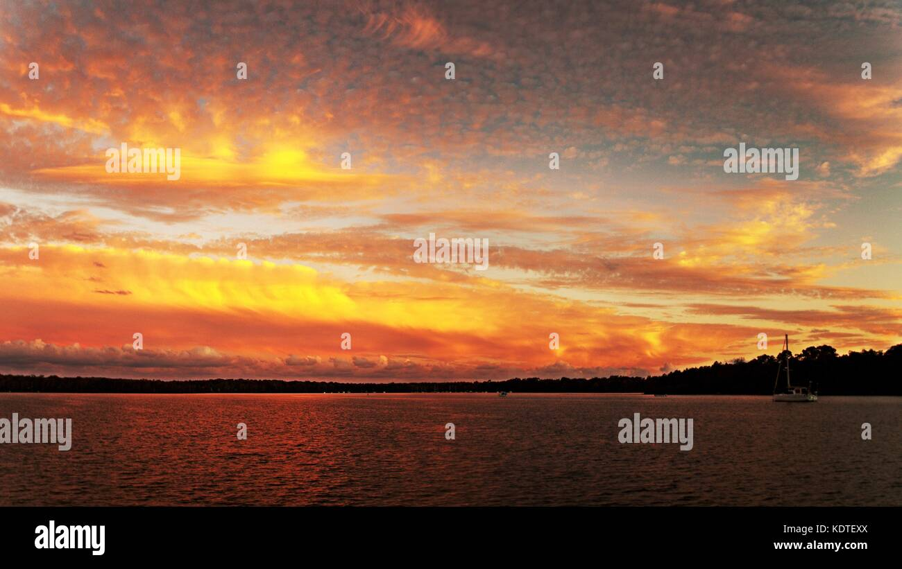 A striking inspirational gold coloured cloudy saltwater lake sunset with water reflections. Captured on Lake Macquarie, - Stock Image