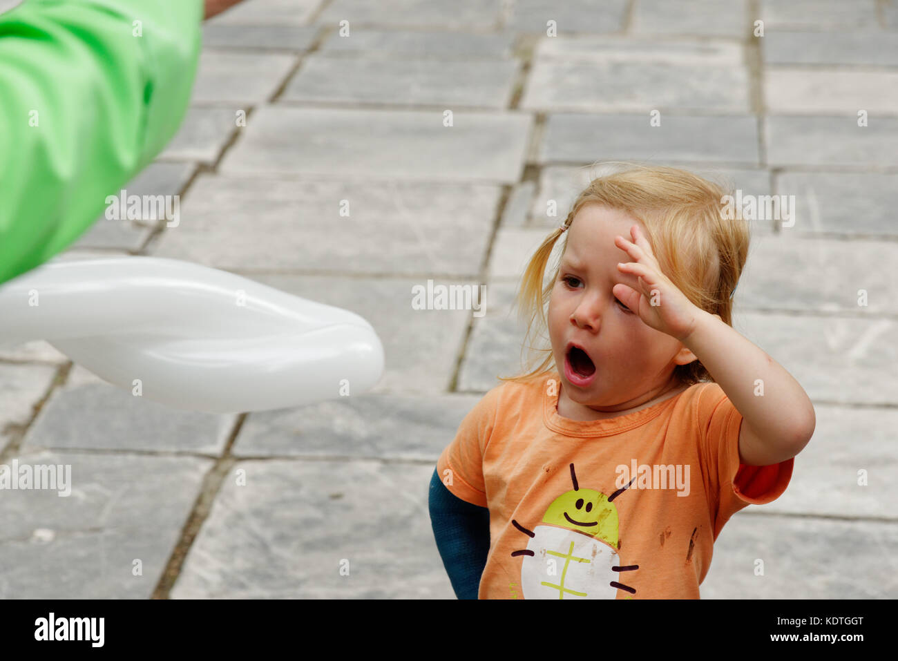 A little girl (3 yrs old) yawning while she watches a balloon sculptor making a balloon. - Stock Image