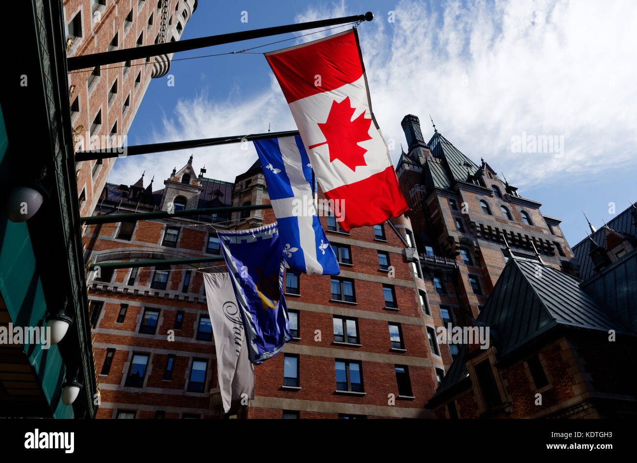 Quebec Flag (Fleur de Lys) and the Canadian flag (Maple Leaf) flying outside the Chateau Frontenac Hotel in Quebec - Stock Image
