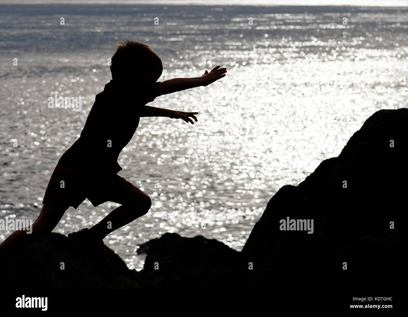 A little boy (5 yrs old) leaping across rocks on the shore of the St Lawrence river at Cap Rouge near Quebec City, - Stock Image