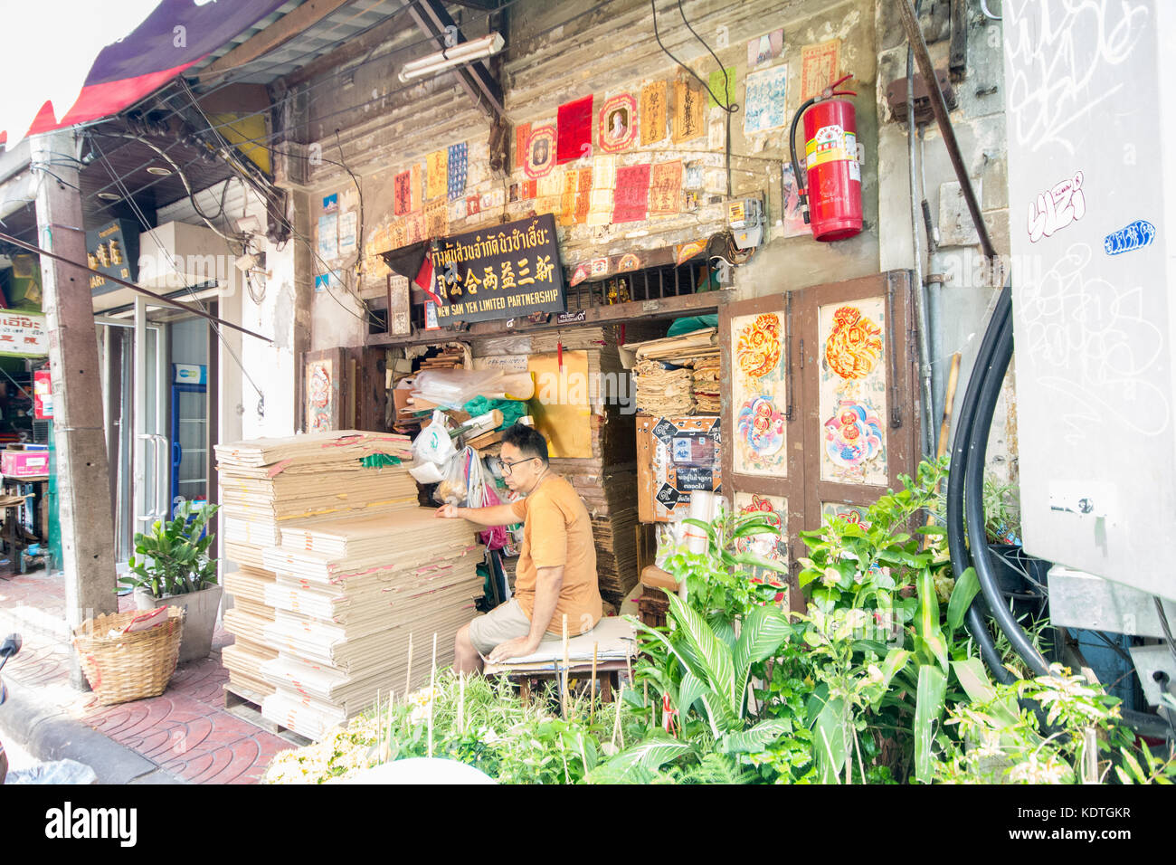 Man sat outside typical business premises, Chinatown, Bangkok, Thailand - Stock Image