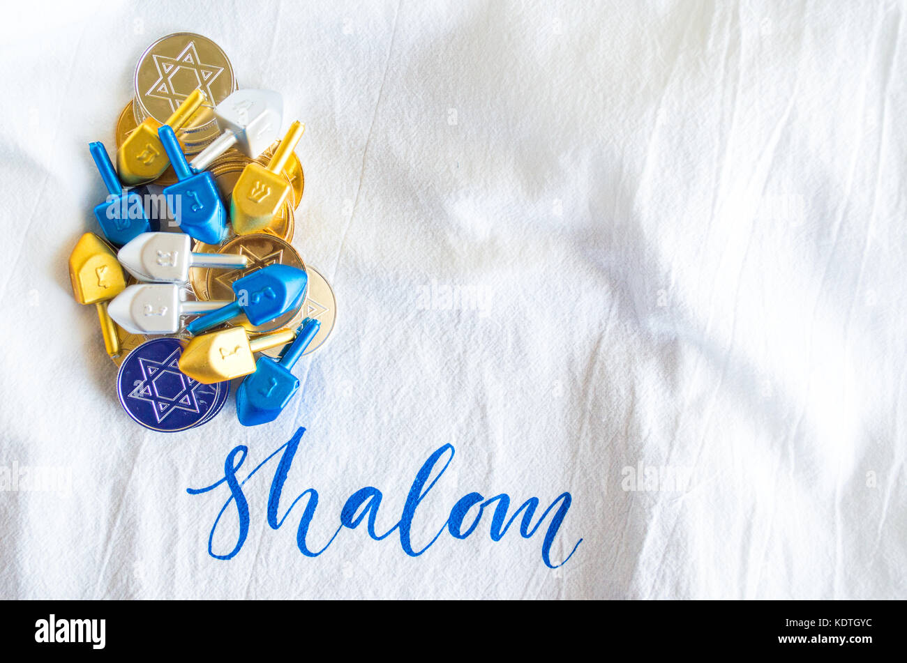 colorful dreidels and Hanukkah coins isolated on a white linen cloth with the word Shalom on it - Stock Image