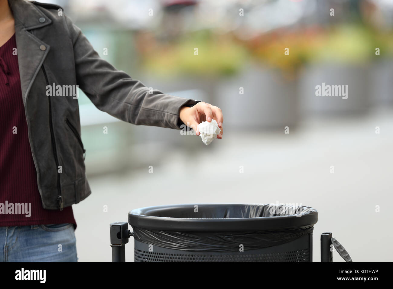 Close up of a lady hand throwing garbage to a trash bin on the street - Stock Image