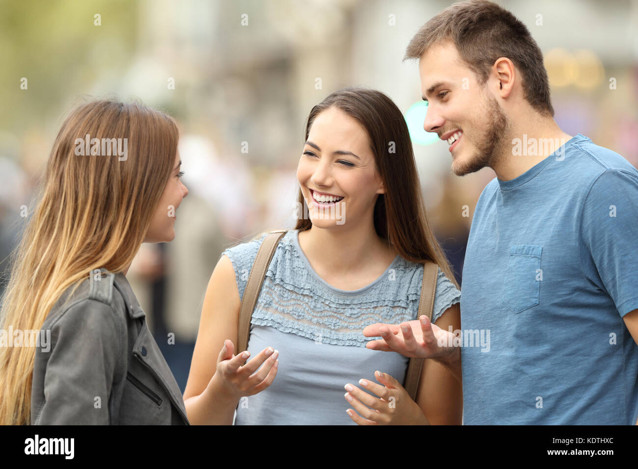 Portrait of three smiling friends talking together standing on the street - Stock Image