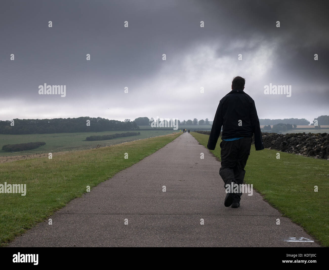 Strolling along the path over the dam at Rutland Water, England, on a dark, cloudy overcast day. - Stock Image