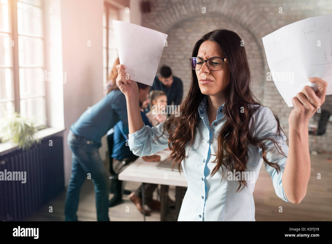 Picture of attractive young angry woman in office - Stock Image
