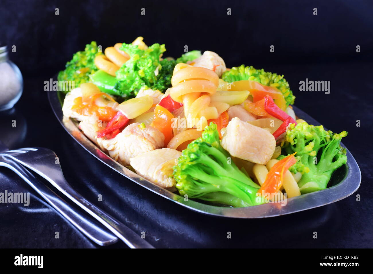 Stir fried chicken fillet with vegetables and pasta on a metal tray on a black abstract background - Stock Image