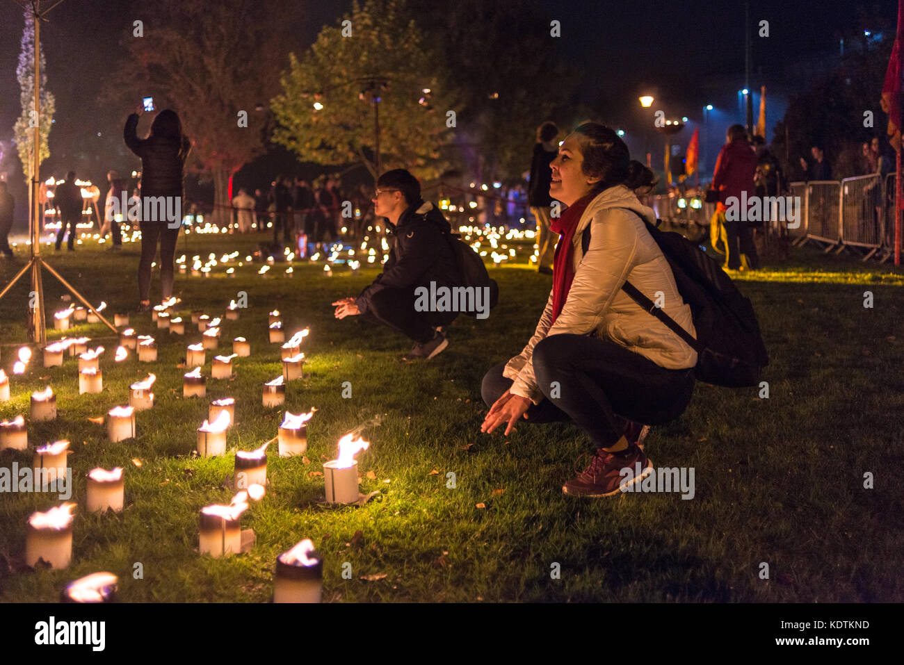 Couple squatting down by candles at Dr. Kronovator's Fire Laboritary active art exhibition at the Arts by the - Stock Image