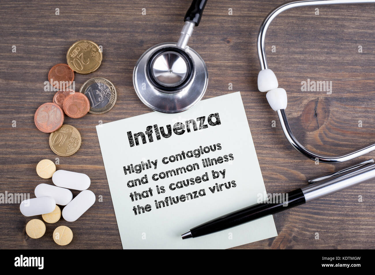 Influenza. Workplace of a doctor. Stethoscope on wooden desk background - Stock Image