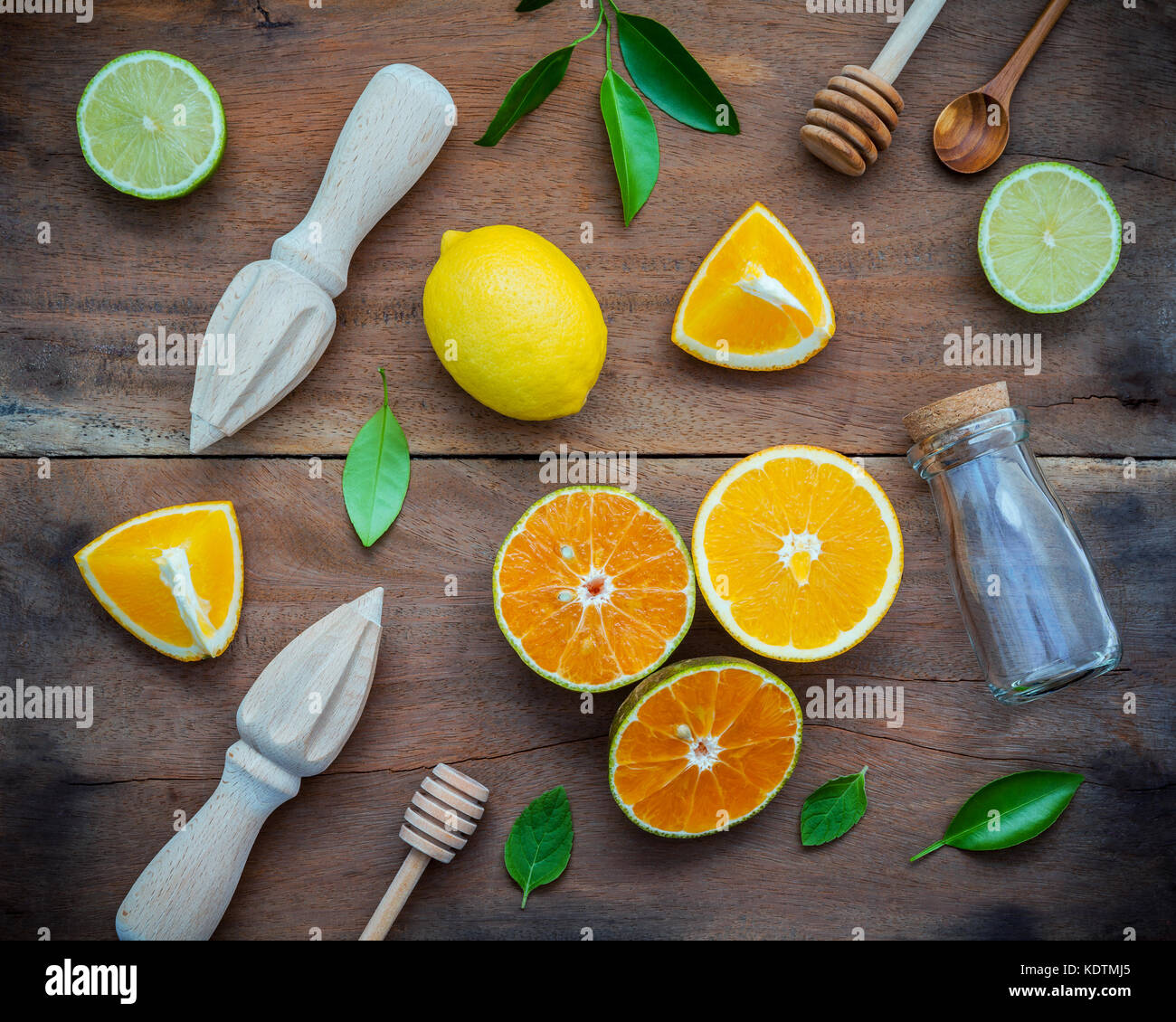 Mixed fresh citrus fruits and orange leaves background. Ingredients for summer citrus juice with juicer and glass - Stock Image