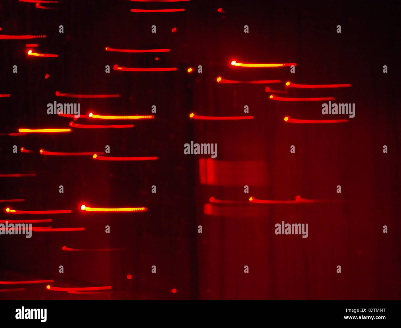 Abstract red lights with low depth of field bokeh on night with motion blur; template/texture with copy space; landscape - Stock Image