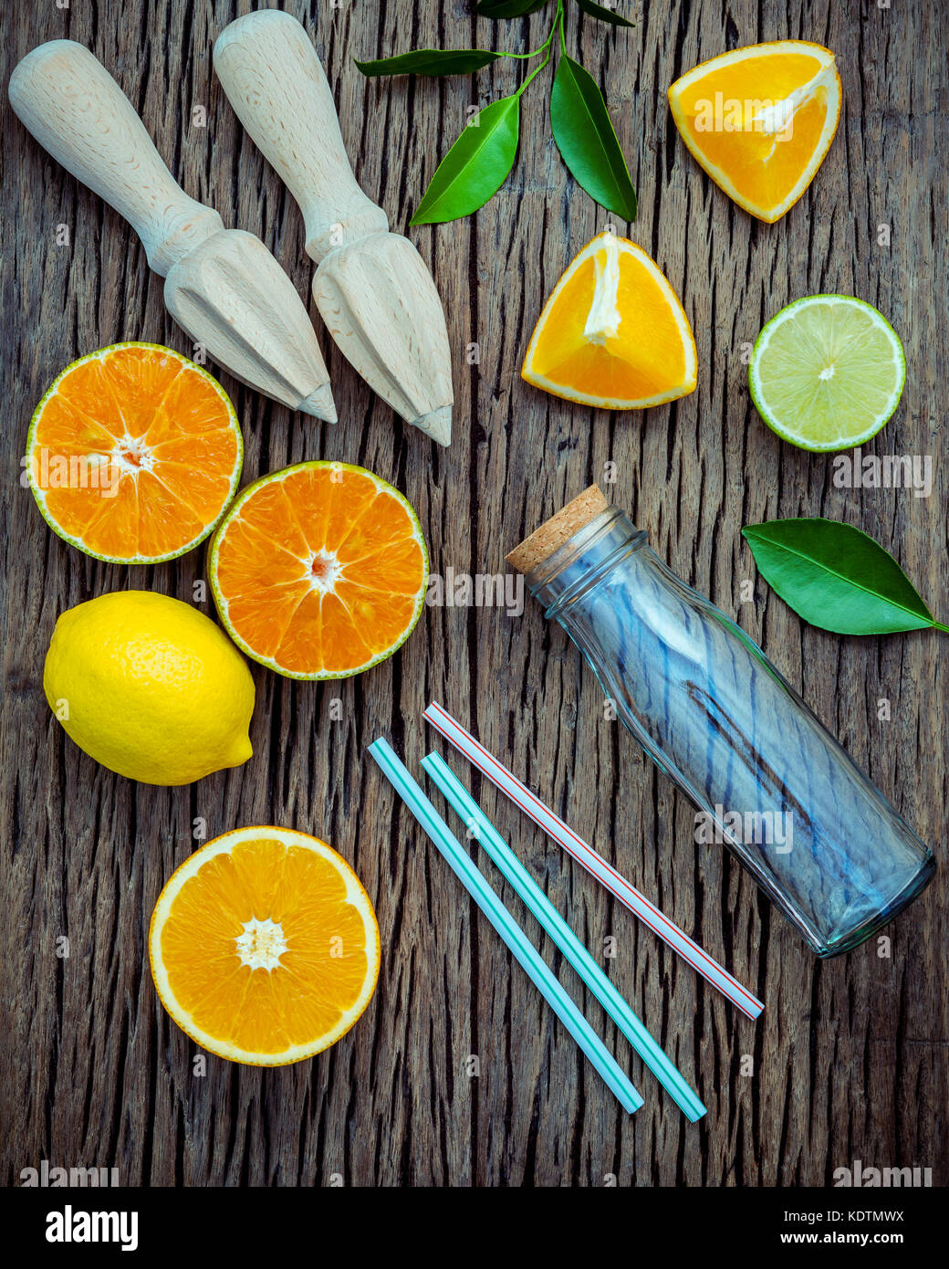 juice with juicer and glass bottle .Fresh lemons, lime and oranges set up on shabby wooden table with flat lay. - Stock Image