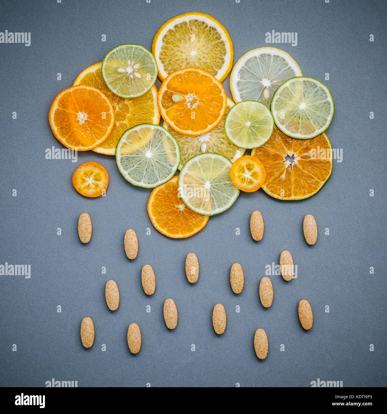 Healthy foods and medicine concept. Pills of vitamin C and citrus fruits in the shape of cloud and raining. Citrus - Stock Image