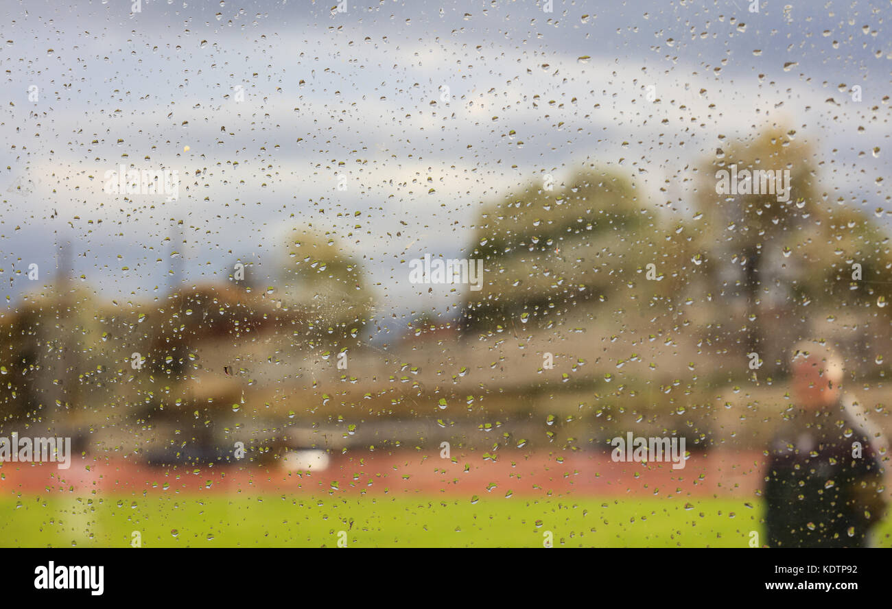 A coach on green grass during a rainy day, view through a glass with tiny raindrops. Abstract and blurred. - Stock Image