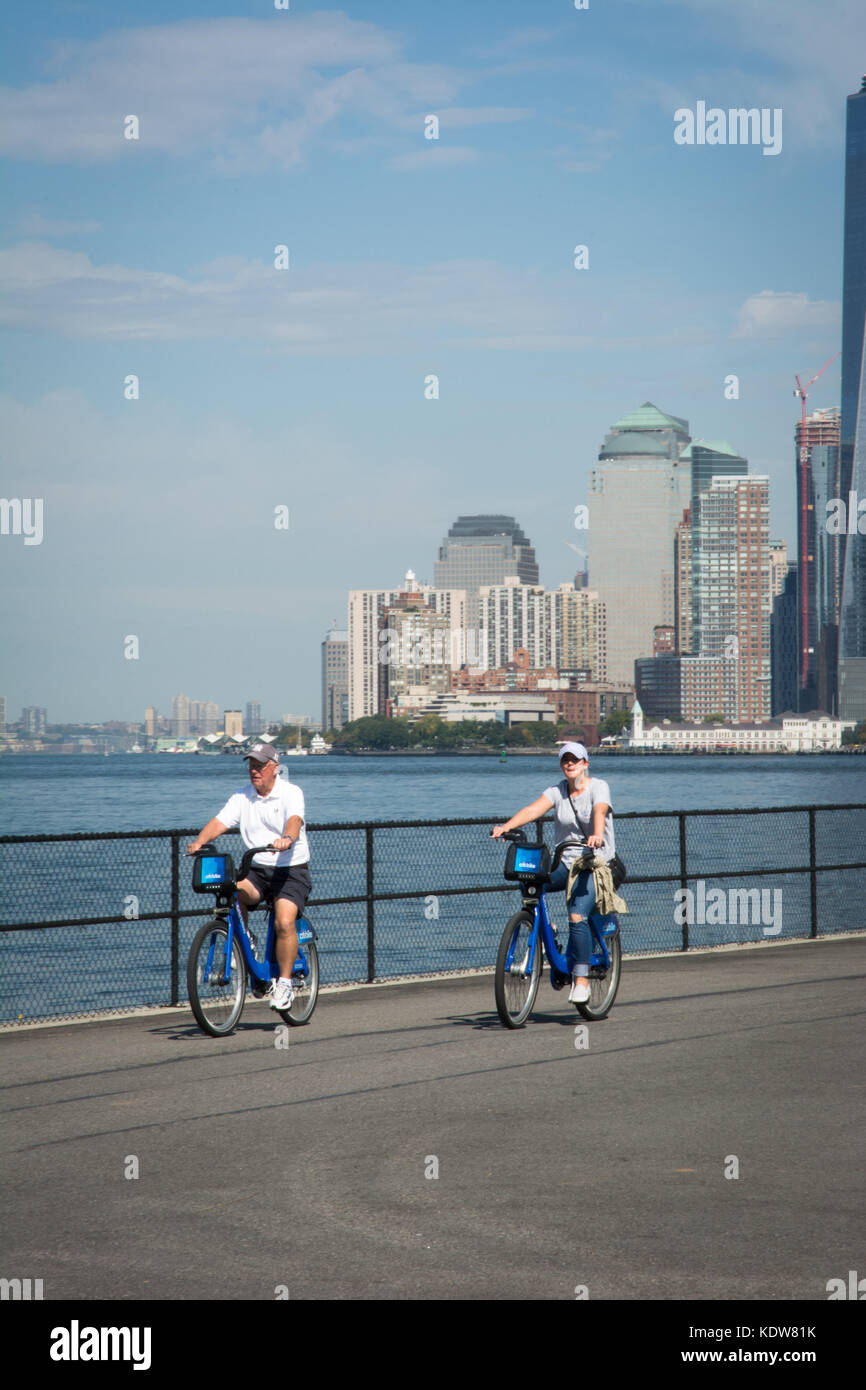 A man and a woman bicycling on Governors Island with New York Harbor and the skyline of lower Manhattan in the background. - Stock Image